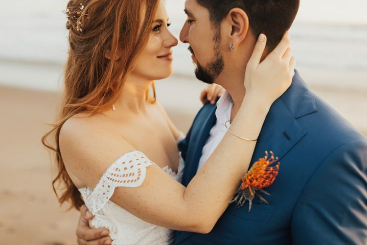 Bride and Groom in Navy Suit with Orange Floral Buttonhole