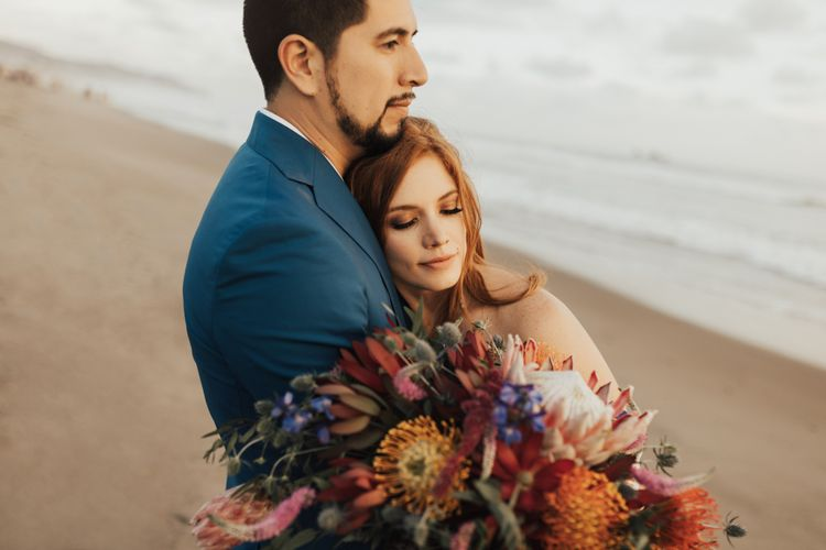 Bride and Groom Embrace With Bright Wedding Flowers