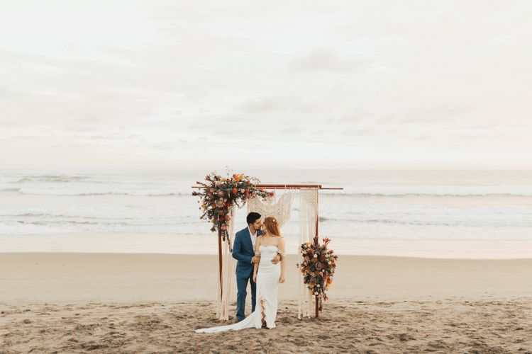 Bride and Groom Under Macrame and Flowers