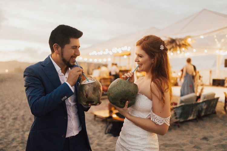 Bride and Groom Drink From Coconuts on Beach