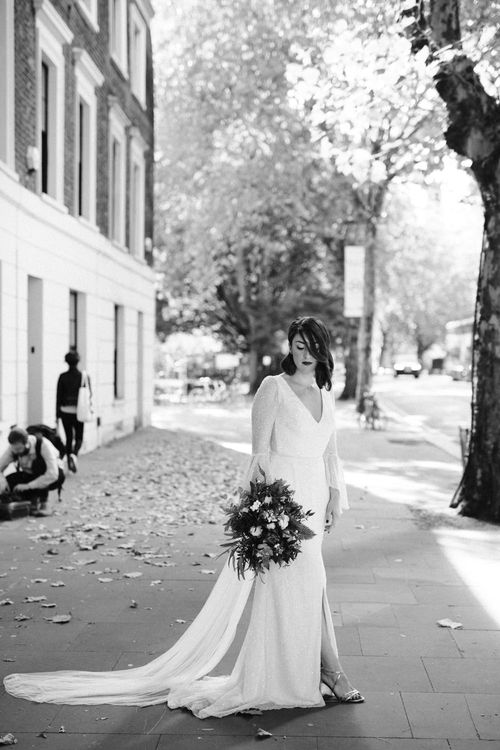 Bride in Sparkly Emma Beaumont Dress with Statement Sleeves, Keyhole Back and Leg Split | Silver Strappy Dune Shoes | Bridal Bouquet of White Roses, White Berries and Foliage | Gin Bike & Monochrome Wedding with Bell Sleeve Emma Beaumont Wedding Dress | Ruth Atkinson Photography