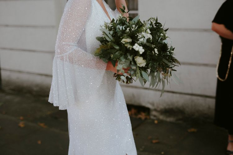 Bride in Sparkly Emma Beaumont Dress with Statement Sleeves, Keyhole Back and Leg Split | Bridal Bouquet of White Roses, White Berries and Foliage | Gin Bike & Monochrome Wedding with Bell Sleeve Emma Beaumont Wedding Dress | Ruth Atkinson Photography