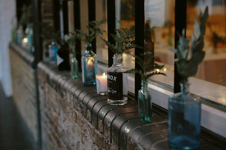 Gin Bottles Filled with Greenery | Diptyque Candles | Islington Metal Works Wedding Reception Venue | Gin Bike & Monochrome Wedding with Bell Sleeve Emma Beaumont Wedding Dress | Ruth Atkinson Photography