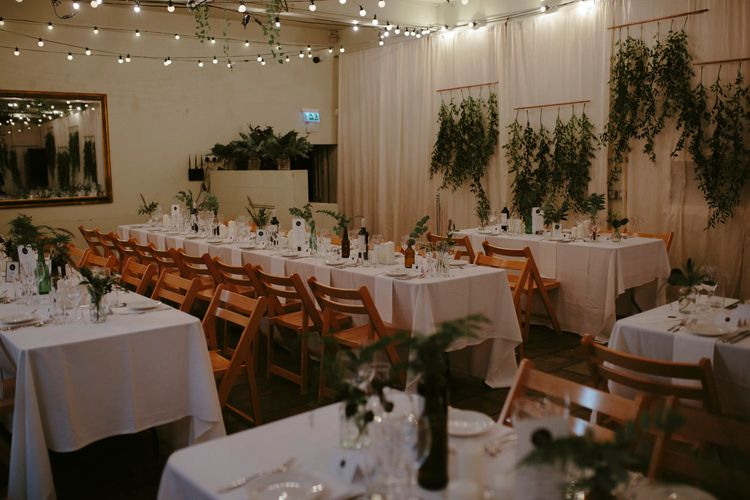 Hanging Greenery | Festoon Lights | Bottles Filled with Foliage | White Pillar Candles | Banquet Tables | Wooden Chairs | Islington Metal Works Wedding Reception Venue | Gin Bike & Monochrome Wedding with Bell Sleeve Emma Beaumont Wedding Dress | Ruth Atkinson Photography