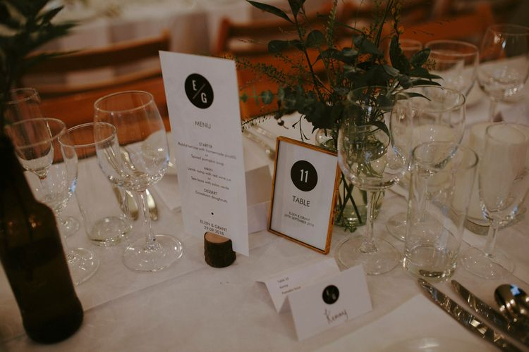 Wedding Breakfast Menu in Log Slice | Table Number in Copper Frame | Foliage in Jar | Islington Metal Works Wedding Reception Venue | Gin Bike & Monochrome Wedding with Bell Sleeve Emma Beaumont Wedding Dress | Ruth Atkinson Photography