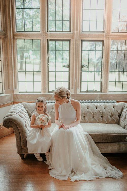 Bride Wears Halterneck Wedding Dress While Talking To Flower Girl