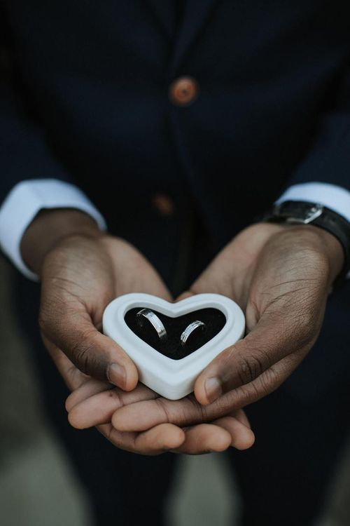 Groom holding heart ring box with wedding bands