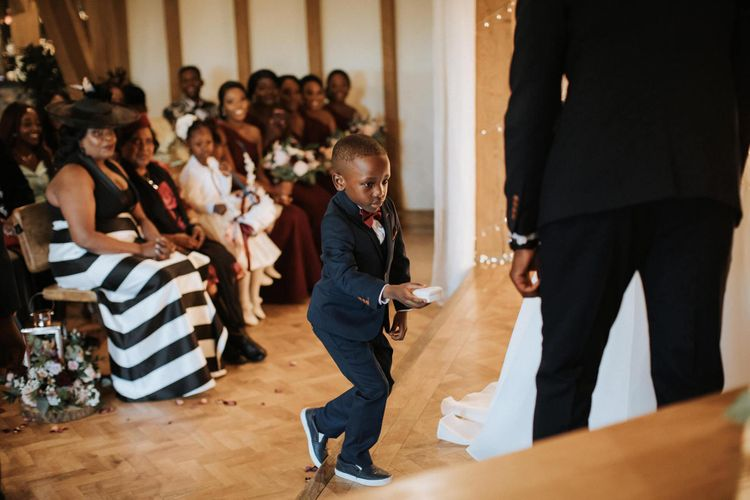 Little boy ring bearer in navy suit at The Old Kent Barn wedding