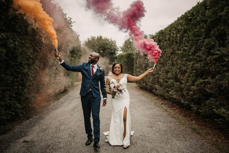 Groom in navy suit and bride in wedding dress with front split holding coloured smoke flares