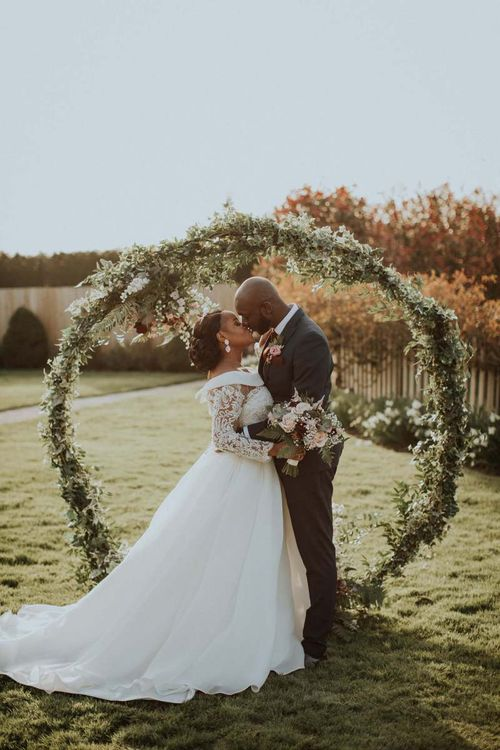 Bride and groom portrait in front of a floral moon gate