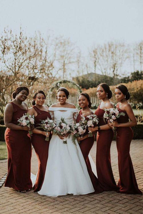 Bridal party portrait with bridesmaids in burgundy dresses at The Old Kent Barn wedding