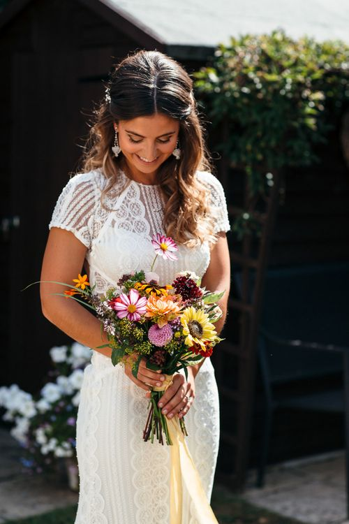 Bride in Lenora Dress by Wtoo Watters with Lace Cap Sleeves and Keyhole Back | Colourful Bridal Bouquet with Sunflowers and Yellow Trailing Ribbon | Macrame Decor, Vintage Caravan Photobooth and Five-Tier Naked Wedding Cake for Boho Wedding in Woodlands | Freckle Photography