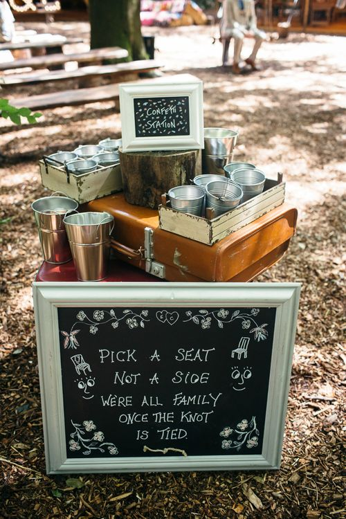 Chalkboard Pick A Seat Not A Side Wedding Sign | Metal Confetti  Buckets | Confetti Station | Vintage Suitcase | Lila's Wood Wedding Venue | Macrame Decor, Vintage Caravan Photobooth and Five-Tier Naked Wedding Cake for Boho Wedding in Woodlands | Freckle Photography