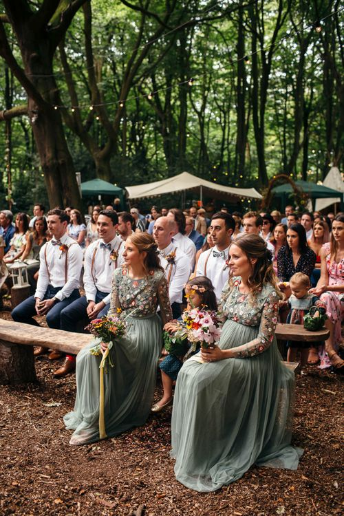 Bridesmaids in Dusky Green Needle & Thread Dresses with Floral Embroidered Bodice and Long Sleeves | Colourful Wedding Bouquets with Sunflowers and Yellow Trailing Ribbons | Groomsmen in Shirts, Braces and Bow Ties | Woodland Wedding Ceremony at Lila's Wood | Macrame Decor, Vintage Caravan Photobooth and Five-Tier Naked Wedding Cake for Boho Wedding in Woodlands | Freckle Photography