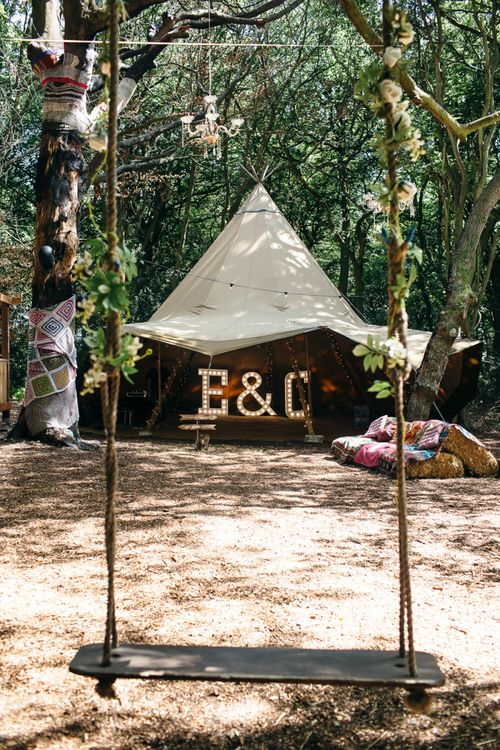 Tipi | Giant Letter Lights | Hay Bales and Blankets | Chandelier Hanging from Trees | Swing | Macrame Decor, Vintage Caravan Photobooth and Five-Tier Naked Wedding Cake for Boho Wedding in Woodlands | Freckle Photography