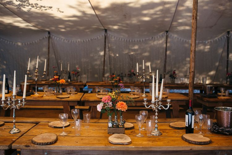 Rustic Wooden Tables | White Tapered Candles | Silver Candlestick Holders | Log Slice Place Settings | Bright Flowers in Glass Bottles | White Bunting | Macrame Decor, Vintage Caravan Photobooth and Five-Tier Naked Wedding Cake for Boho Wedding in Woodlands | Freckle Photography