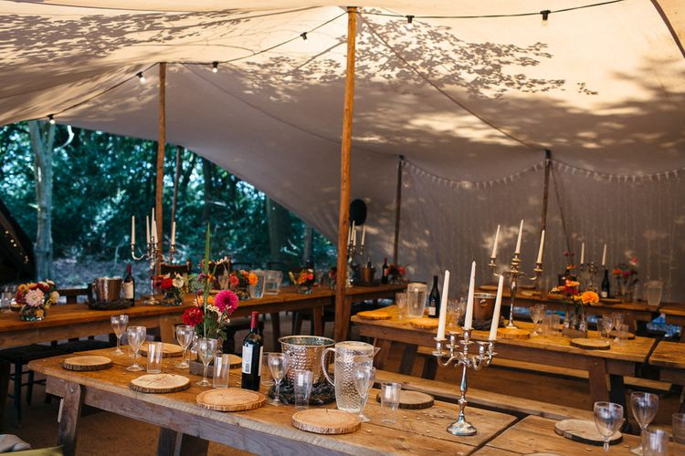 Rustic Wooden Tables | White Tapered Candles | Silver Candlestick Holders | Log Slice Place Settings | Bright Flowers in Glass Bottles | White Bunting | Silver Wine Buckets | Macrame Decor, Vintage Caravan Photobooth and Five-Tier Naked Wedding Cake for Boho Wedding in Woodlands | Freckle Photography