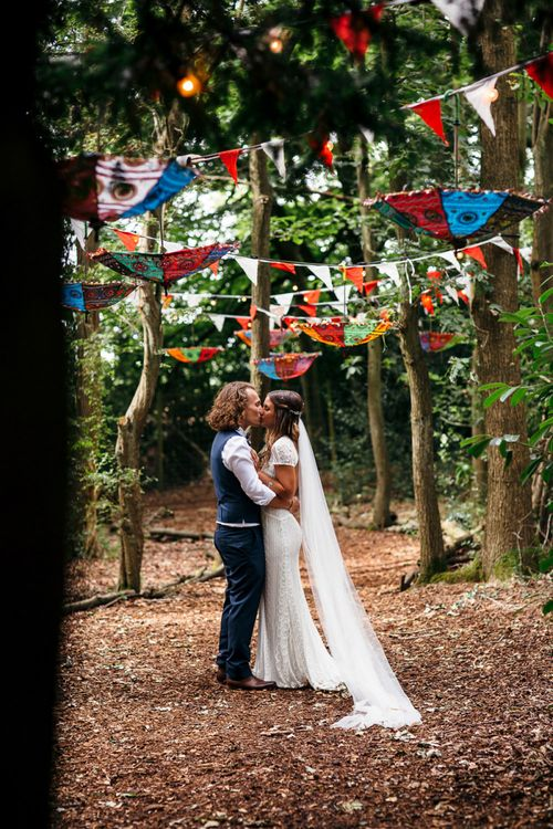 Bride in Lenora Dress by Wtoo Watters with Lace Cap Sleeves and Keyhole Back | Groom in Blue Waistcoat and Trousers with Colourful Patterned Bow Tie | Colourful Bunting | Hanging Upside Down Umbrellas | Macrame Decor, Vintage Caravan Photobooth and Five-Tier Naked Wedding Cake for Boho Wedding in Woodlands | Freckle Photography
