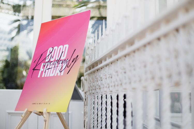 Bright wedding signs contrasting to the white bridesmaid dresses
