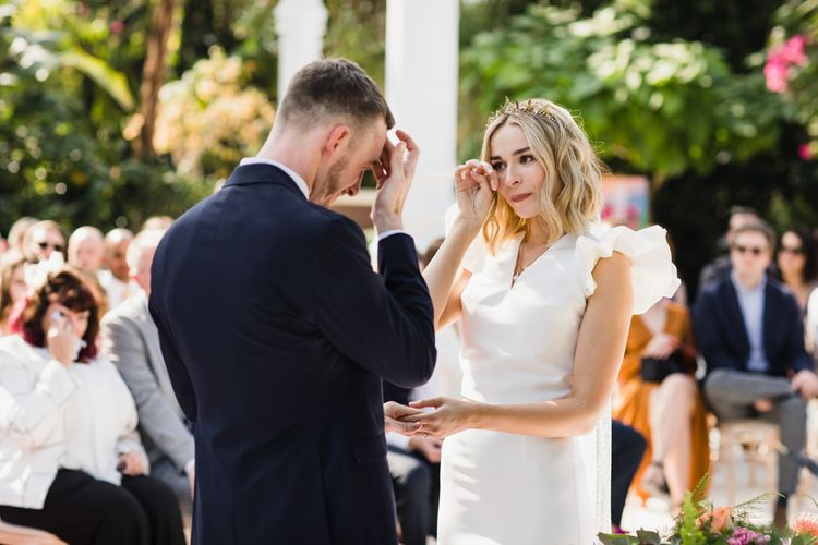 Bride wipes tear as they exchange vows