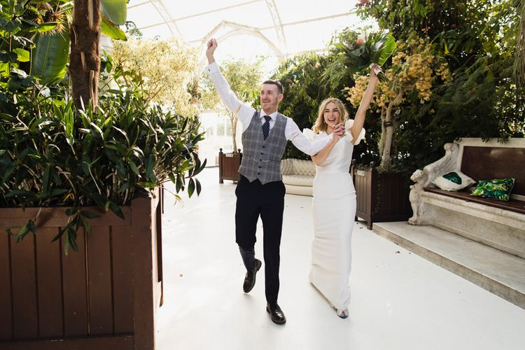 Bride and groom celebrate their wedding with white bridesmaid dresses
