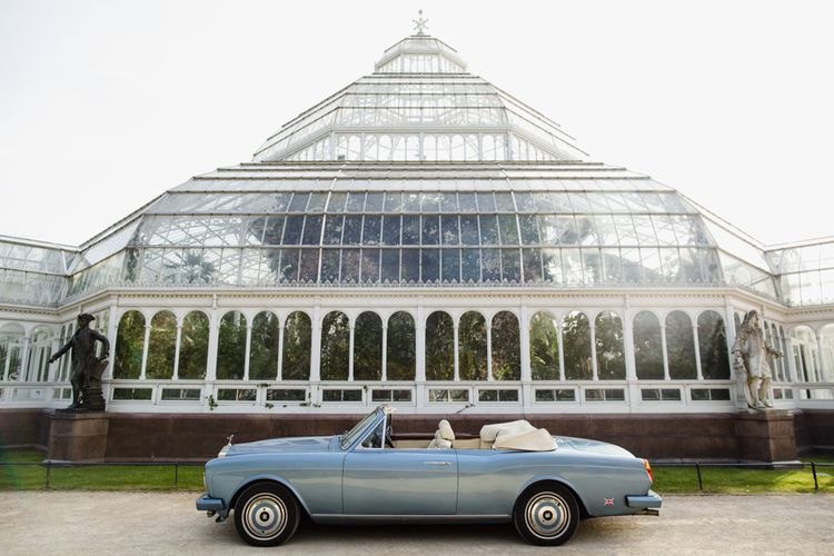Wedding car parked in front of glass house wedding venue