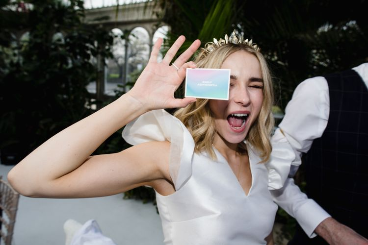 Bride wears crown and holds up bright place name card