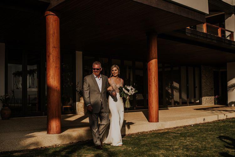 Bride is escorted to wedding ceremony