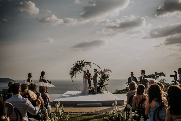 Bride and groom during Thailand wedding ceremony with amazing views and moon gate decor