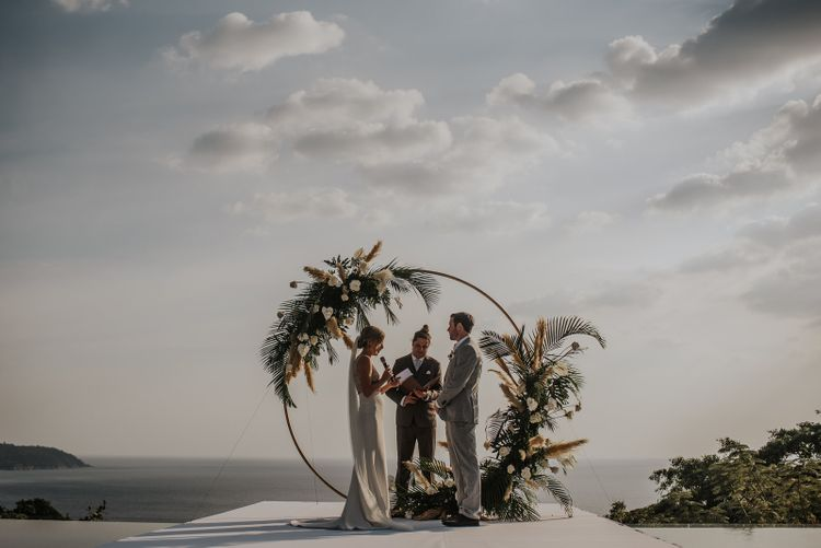 Bride and groom during intimate Thailand wedding ceremony with amazing views and moon gate decor and pampas grass