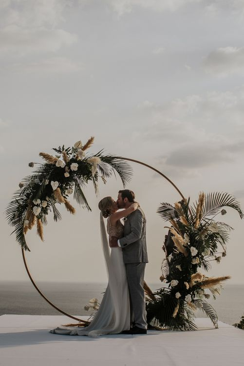 Bride and groom during Thailand wedding ceremony with amazing pampas grass and moon gate decor