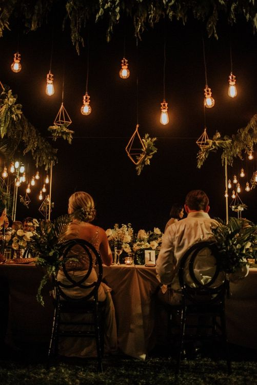 Bride and groom at intimate Thailand wedding with hanging lights and geometric decor