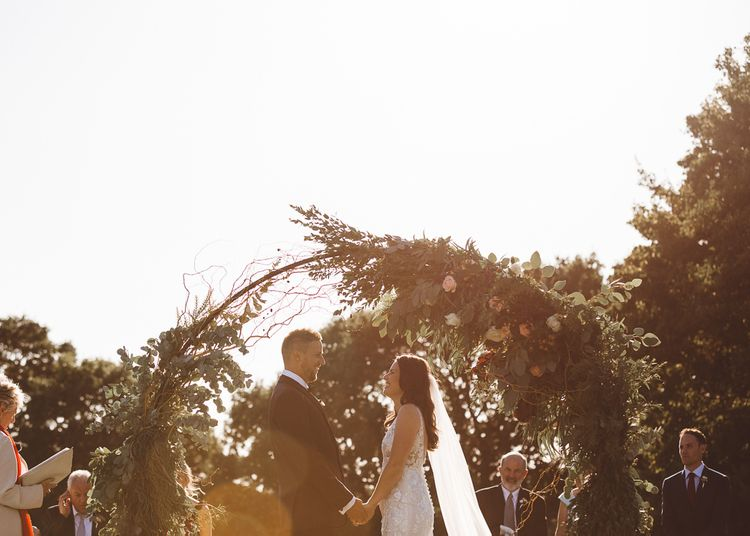 Beautiful floral and foliage hoop decor at intimate outdoor ceremony