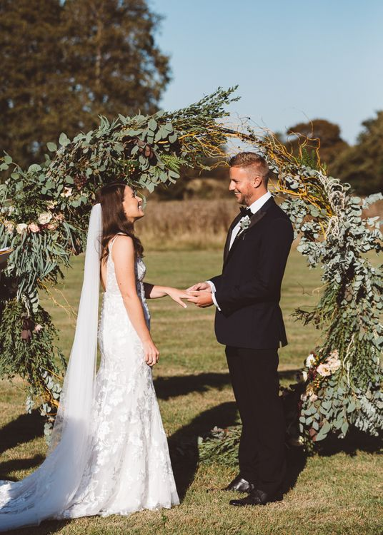 Bride and groom tie the knot at Crouchers Orchards with hoop foliage decor