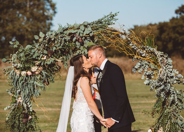 Bride and groom say 'I do' with foliage hoop decor for intimate outdoor ceremony