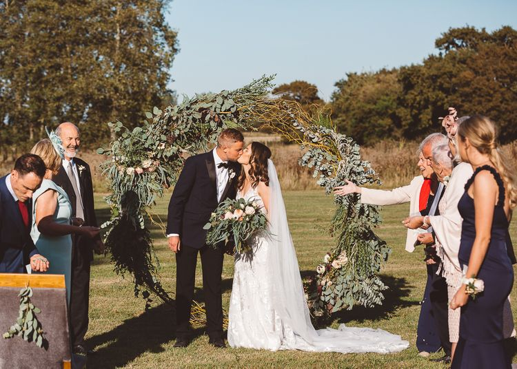 Intimate wedding ceremony at Crouchers Orchards with foliage hoop decor and eucalyptus chair decor
