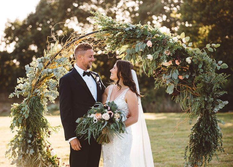 Bride wearing beautiful Made With Love Bridal dress and groom wearing black tie suit