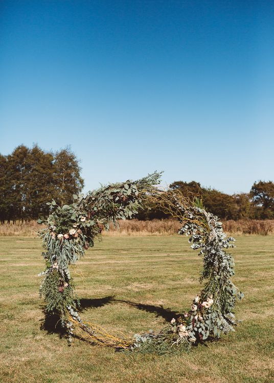 Aisle hoop decor styled with eucalyptus and foliage at Crouchers Orchards for outdoor ceremony