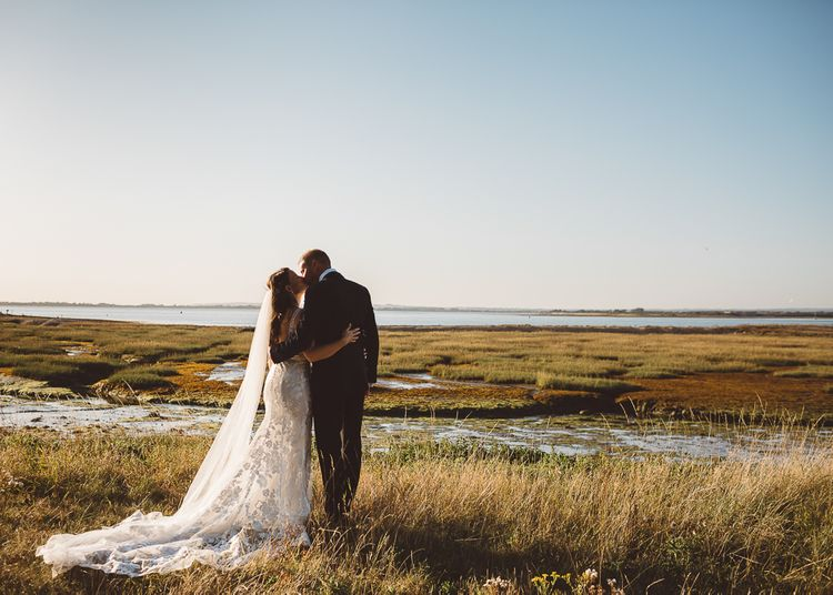 Bride and groom embrace at outdoor wedding