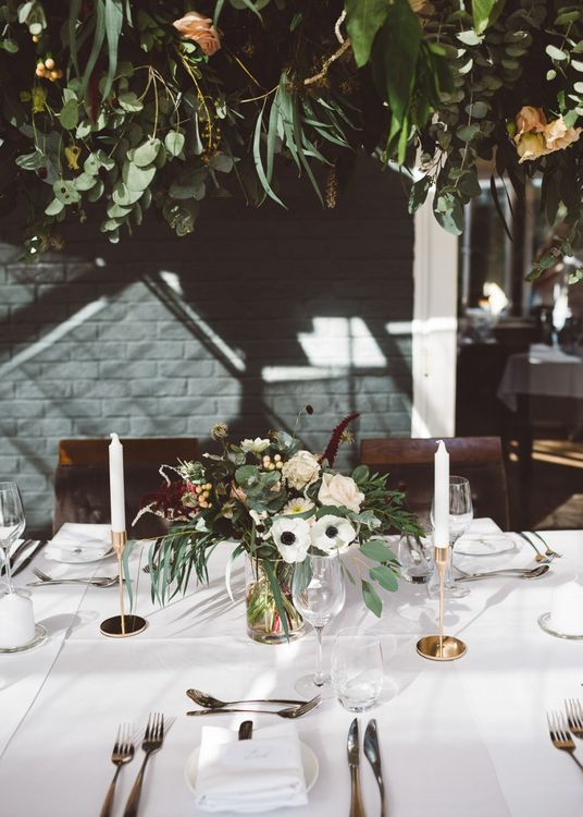 Hanging foliage and floral table arrangements styled with gold candlesticks for intimate dinner