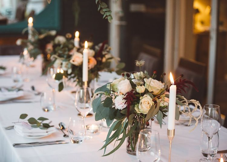 Beautiful hanging foliage styled with eucalyptus and gold candlesticks for a romantic and intimate dinner