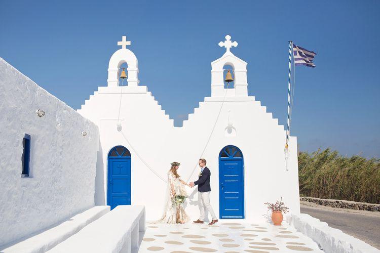 Boho Bride in Ruse De Seine Wedding Dress and Groom in Chinos and Blazer Holding Hands in Mykonos