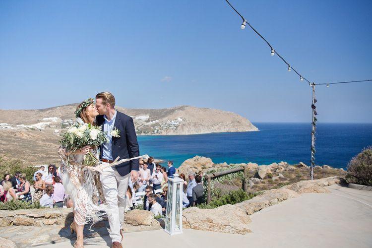 Bride in Rue De Seine Dakota Wedding Dress with Fringe and Groom in Chino's and Navy Blazer Kissing
