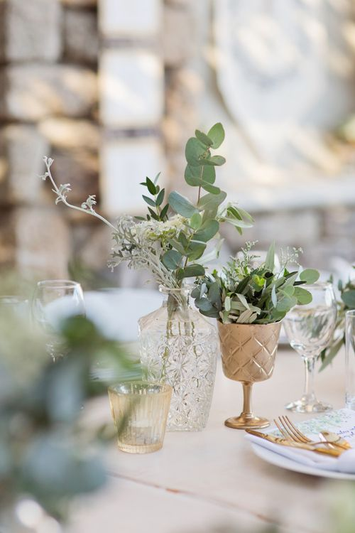 Glass Decanter and Gold Goblets Filled with White Flowers and Foliage