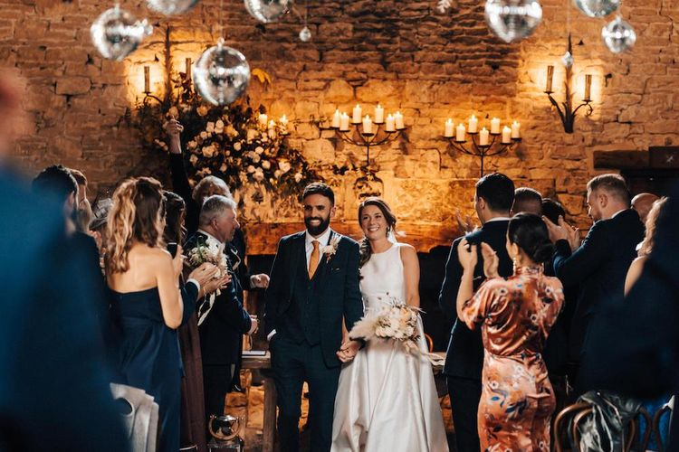 Newlywed bride and groom at October wedding with glitter ball decor