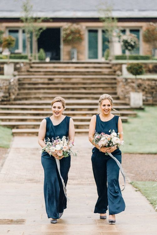 Bridesmaids walking down the aisle in navy blue jumpsuits at Yorkshire Wedding Barn