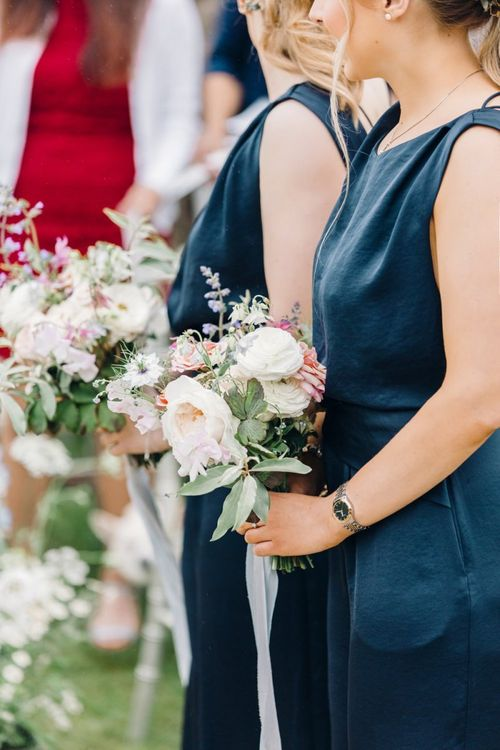 Bridesmaids in navy jumpsuits holding bouquets
