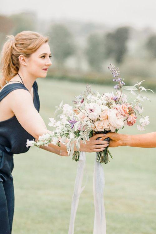 Bride handing her romantic bouquet to her bridesmaid