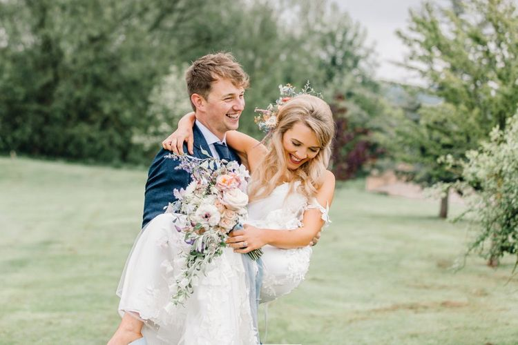 Groom in navy suit picking up his bride at Yorkshire Wedding Barn