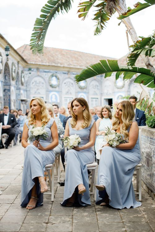Bridesmaids in Pale Blue Dresses with Wavy Hair and White Bouquets
